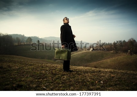man standing with green suitcase on a meadow smoking and waiting