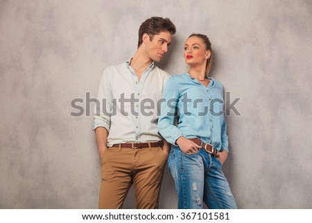 man standing with hands in pockets in studio background stares at woman while she pose looking away - stock photo