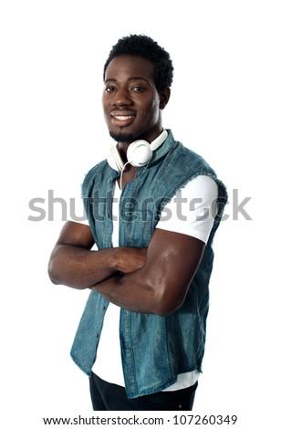 Man standing with headphones around his neck, arms crossed half length portrait - stock photo