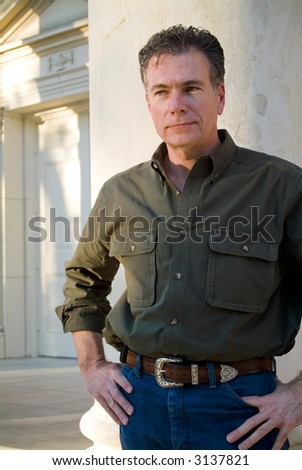 man, standing with his hands in his pockets on the steps of a church as if waiting impatiently. - stock photo