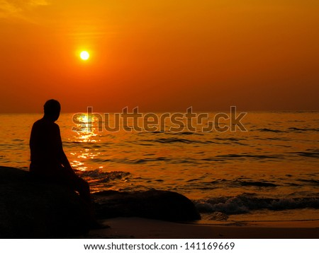 man stands alone watching the sunset