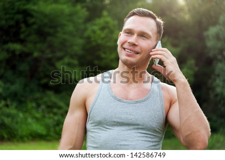 Man stands and talking on a telephone in the park - stock photo