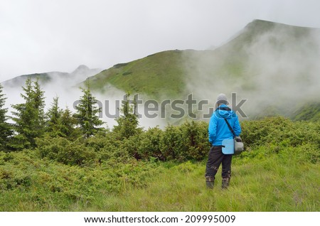 Man stands at the foot of the mountain. Cloudy weather with clouds  - stock photo
