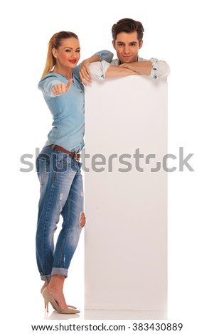 man stands behind white blank billboard with hands crossed while woman shows thumbs up sign in isolated studio background - stock photo