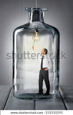 man stands in a bottle and turns on the light - stock photo