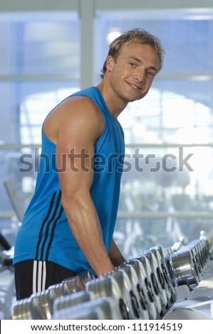Man stands in front of dumbbells on rack at gym - stock photo