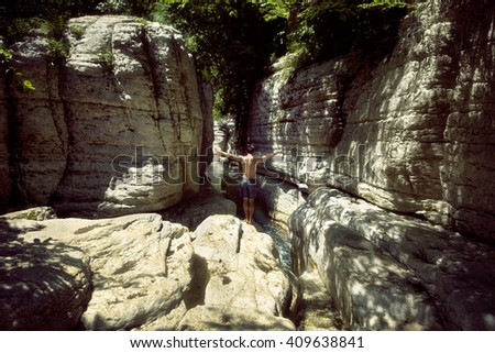 Man stands in the canyon. He is going to jump and swim in the river. Georgia. - stock photo