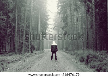 Man stands in the fog in the forest - stock photo