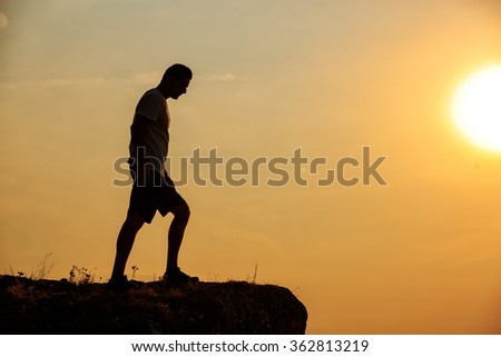 Man stands near the cross on top of mountain - stock photo
