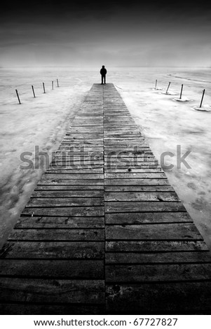 Man stands on a pier - stock photo