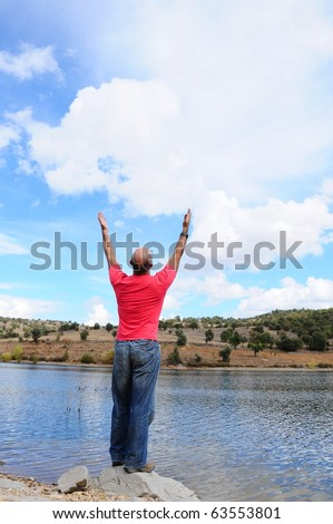 man stands on a rock by lake