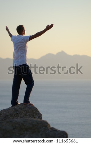 Man stands on a rock by the sea with his arms raised to the sky - stock photo