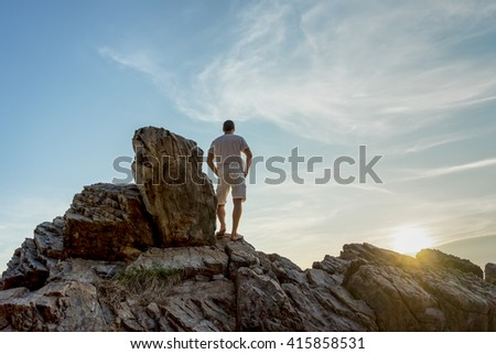 Man stands on a rocks watching tropical sunset