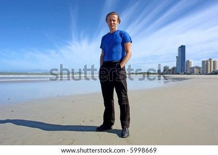 Man stands on beach with majestic sky and sky-scrapers. Shot in Strand, Western Cape, South Africa.