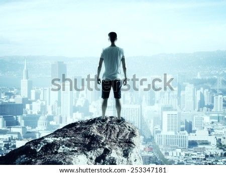man stands on top mountain and looking to city - stock photo