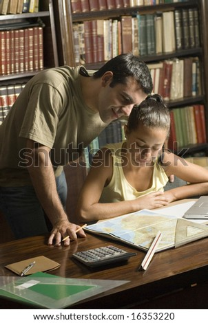 Man stands over woman. She is sitting at the table looking at a map. Vertically framed photo. - stock photo