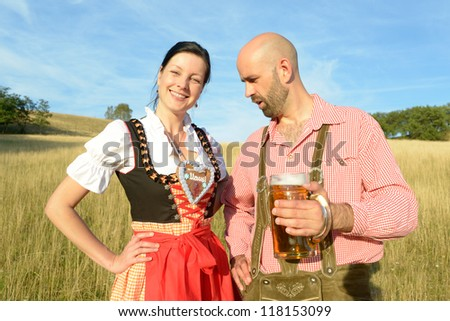 man staring at the decollete of a happy woman in traditional bavarian garbs - stock photo