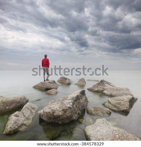 Man staring at the sea. - stock photo