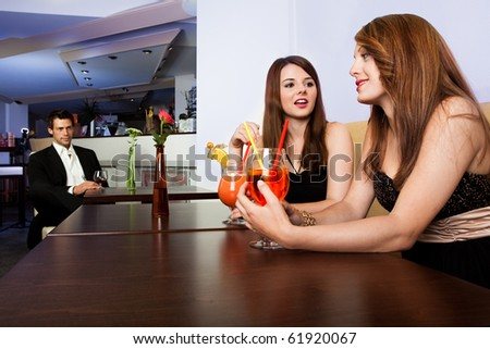 Man staring at two female friends talking.