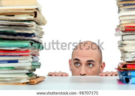 Man staring nervously at piles of folders - stock photo