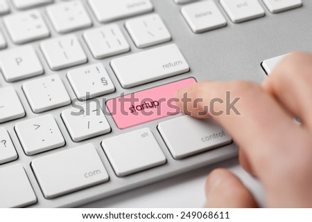 Man start his online startup business. Startup word on keyboard.  - stock photo