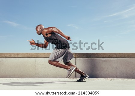 Man start running on the pathway with the blue sky in the background and copy space around him. Motion blur.   - stock photo
