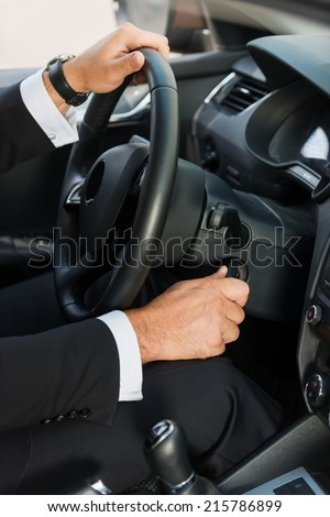 Man starting a car. Close-up of man in formalwear starting a car