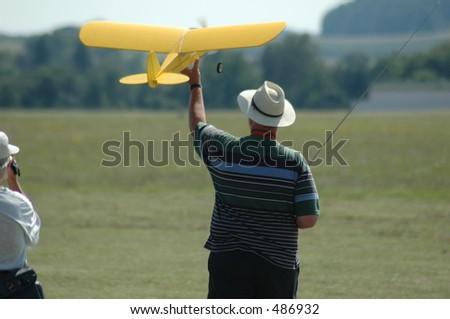 man starting radio controled airplane - stock photo