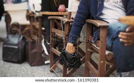 Man stealing wallet from the woman's purse at street cafe during daytime. Pickpocketing at the street cafe - stock photo