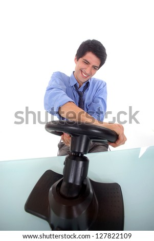 Man steering a wheel in his office. - stock photo