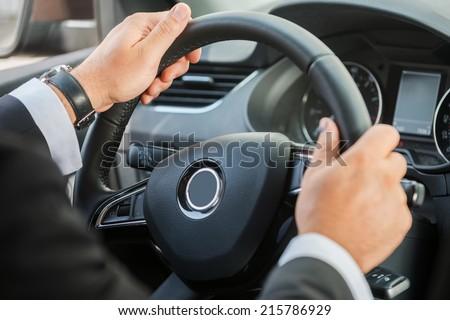 Man steering wheel. Close-up of man in formalwear driving car  - stock photo