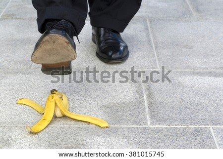Man stepping on banana peel skin, copy space, work accident concept - stock photo