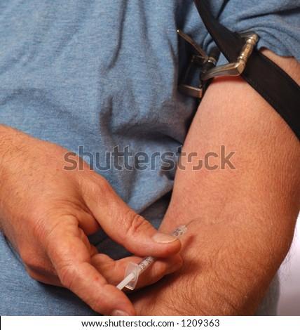 Man sticking needle into arm - stock photo