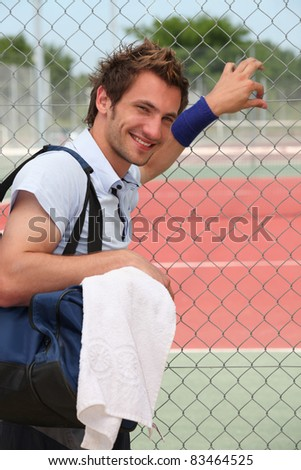 Man stood by tennis court - stock photo
