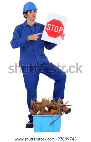 Man stood holding stop sign by crate of refuge - stock photo