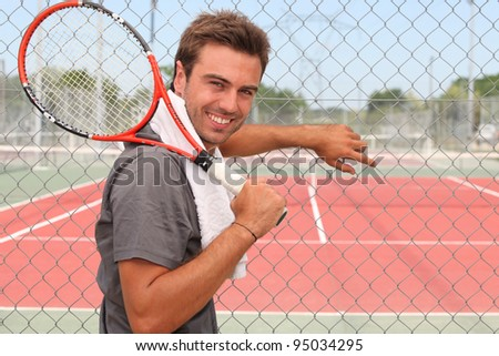 Man stood in front of tennis court holding racket over shoulder - stock photo
