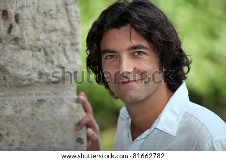 Man stood outdoors by stone wall - stock photo