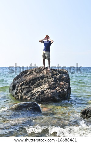 Man stranded on a rock in ocean calling for help - stock photo