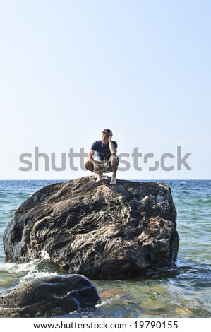 Man stranded on a rock in ocean waiting for rescue - stock photo