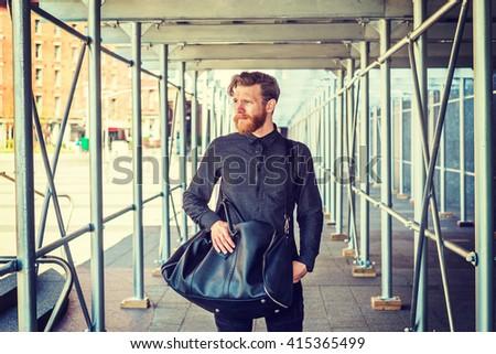 Man street casual fashion. American man with beard, mustache traveling in New York, wearing black shirt, shoulder carrying leather bag, walking through sidewalk bridge. Instagram filtered effect. - stock photo