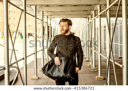 Man street casual fashion. American man with beard, mustache traveling in New York, wearing black shirt, shoulder carrying leather bag, walking through sidewalk bridge. Color filtered look.  - stock photo