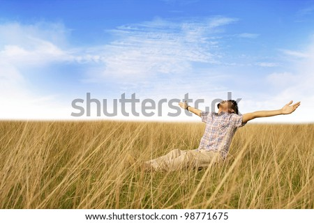 Man stretch his hands enjoying freedom sitting on the meadow