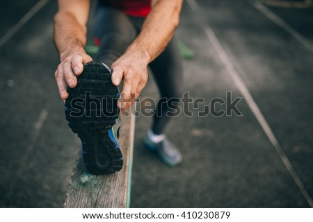 man stretches the body before running - stock photo