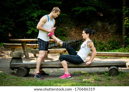Man stretches womans leg - muscle spasm after sport training - stock photo