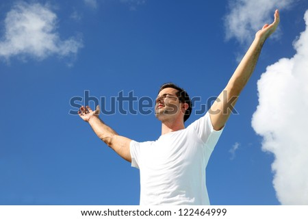 Man stretching arms up towards the sky - stock photo