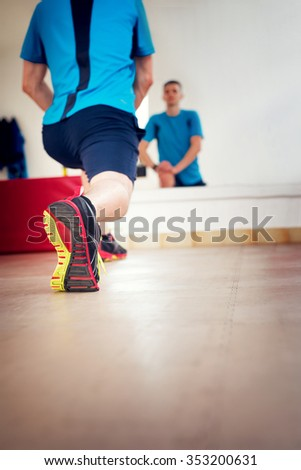 Man stretching at gym. Shallow depth of field with focus on sneakers.