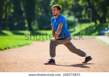 Man stretching body, warming up for jogging