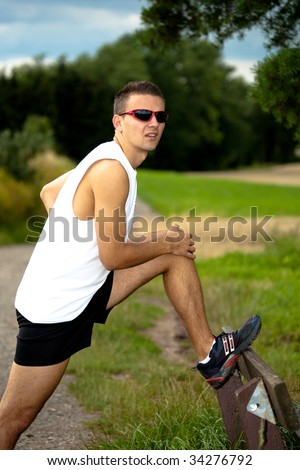 man stretching for jogging through the fields