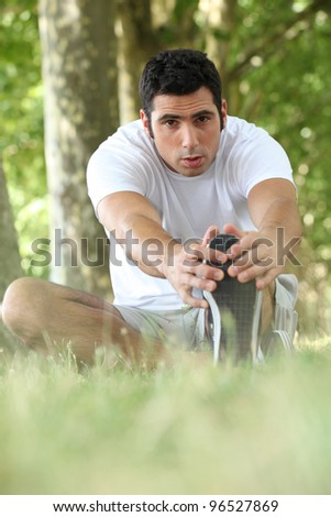 Man stretching in the forest - stock photo