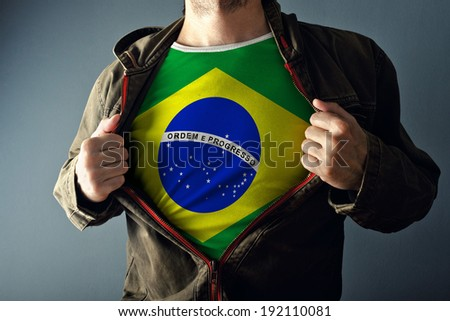 Man stretching jacket to reveal shirt with Brazil flag printed. Concept of patriotism and national team supporting. - stock photo